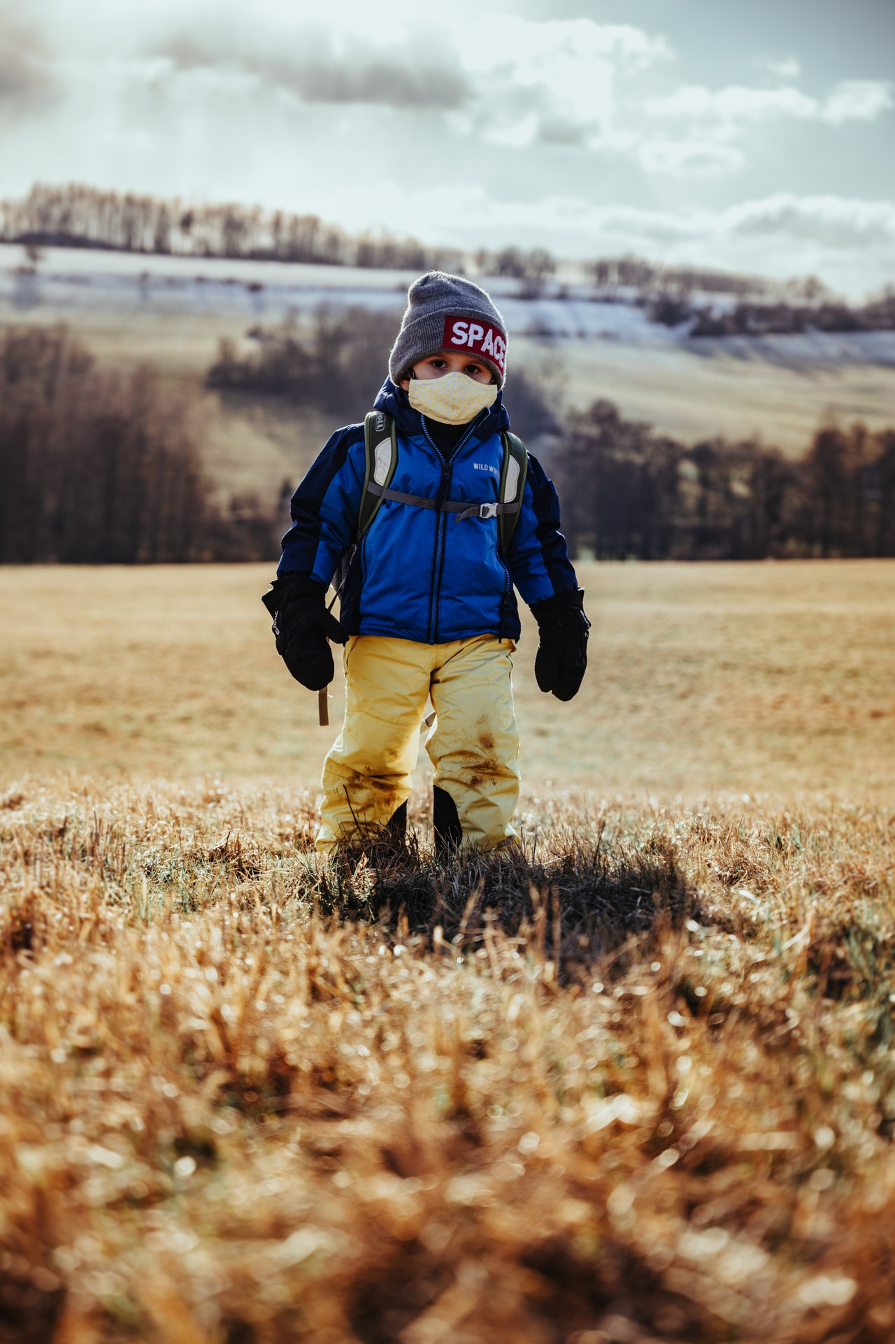 kid-in-blue-jacket-and-brown-pants-walking-on-brown-grass-3989786 1