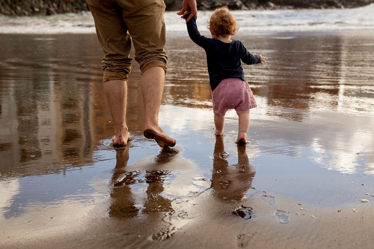 father-and-child-walking-on-the-shore-3968107 1